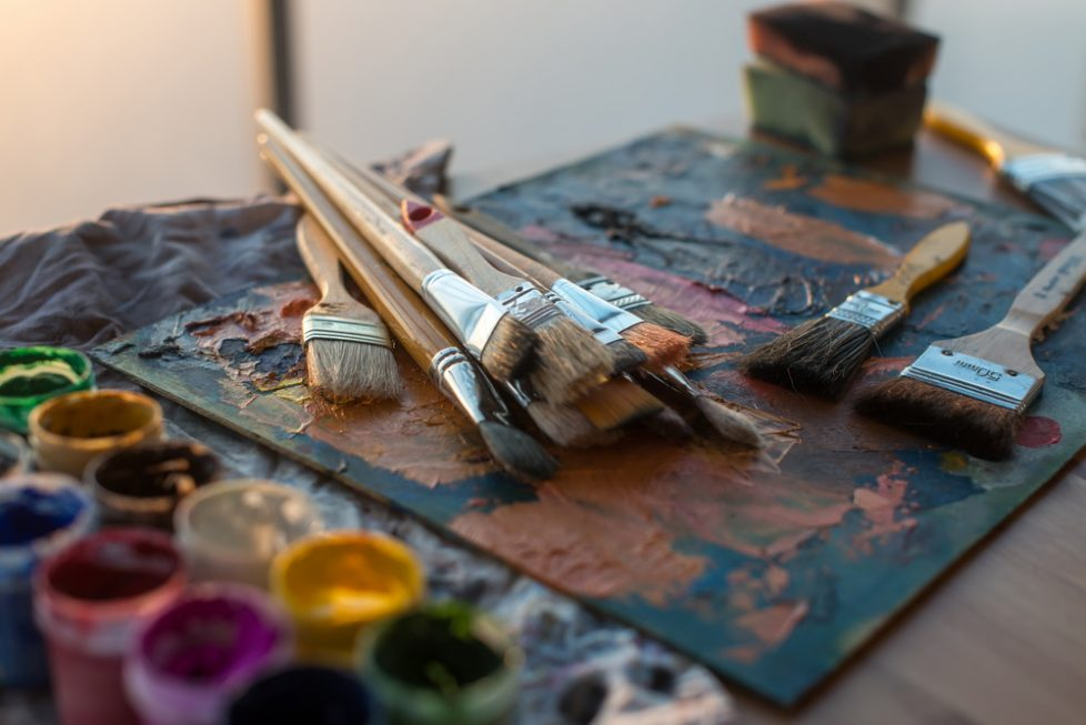 Drawing classes tools in art studio. Angle view photo of paintbrushes lying on palettewith oil paints brushstrokes mixture.